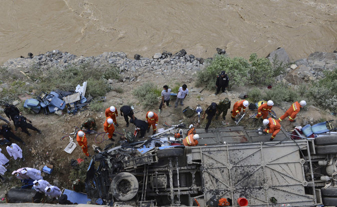 Rescuers worked around an overturned tour bus after it fell off a cliff in Tibet. Credit Chogo/Xinhua, via Associated Press