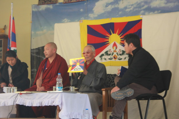 Narkyid Ngawang Dhondup explaining the Tibetan national flag's historical back ground, flanked by Namgyal Dolkar Lhagyari (far left), Geshe Monlam Tharchin (left) and Dorjee Tseten (right).