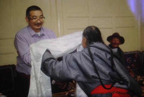 Labrang Jigme receiving a traditional Tibetan scarf from a well wisher.
