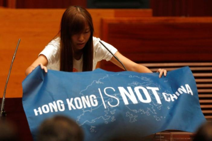 Newly elected lawmaker Yau Wai-ching displays a banner before taking oath at the Legislative Council in Hong Kong, China October 12, 2016.  REUTERS/Bobby Yip